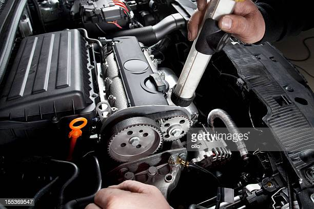 Mechanic is checking the timing belt of a modern car