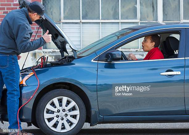 Mechanic jumping battery for woman in car