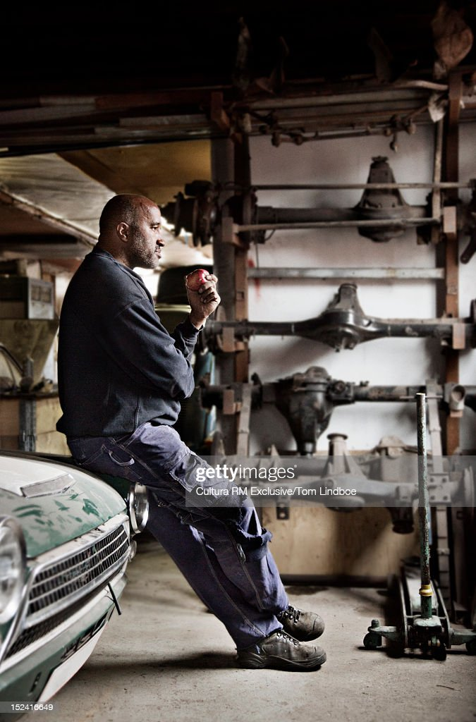 Mechanic leaning on car in garage