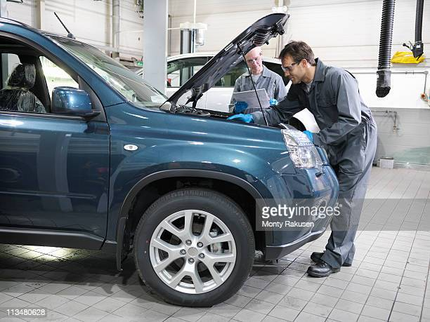 Mechanic looking at paper and second mechanic analyzing engine, bonnet open, in car dealership workshop