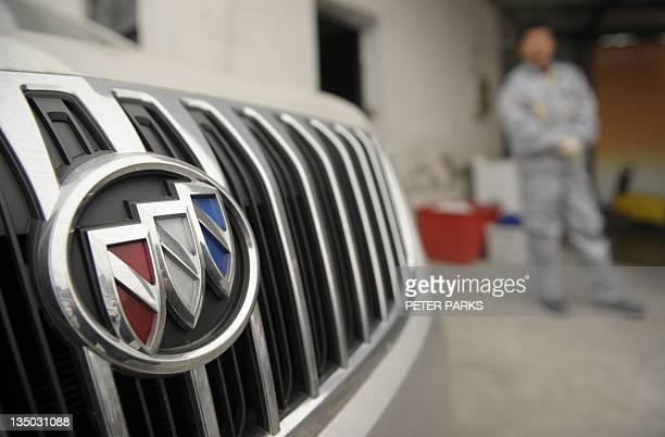 A mechanic looks at a Buick at a General Motors dealership in Shanghai on December 6 2011 The US auto giant said its sales in China surged more than...