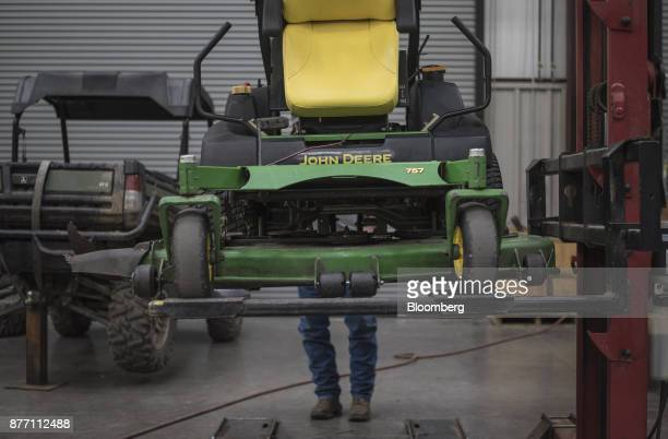 A mechanic lowers a Deere Co John Deere 757 lawn mower at a United Ag Turf dealership in Waco Texas US on Monday Nov 20 2017 Deere Co is scheduled to...