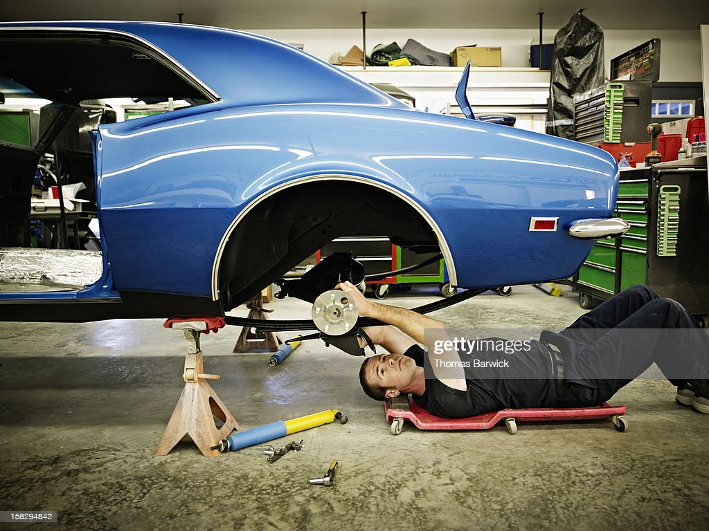 Mechanic lying on floor in garage working on car : Stock Photo