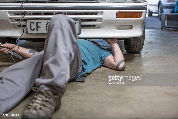 Mechanic lying on floor working on car