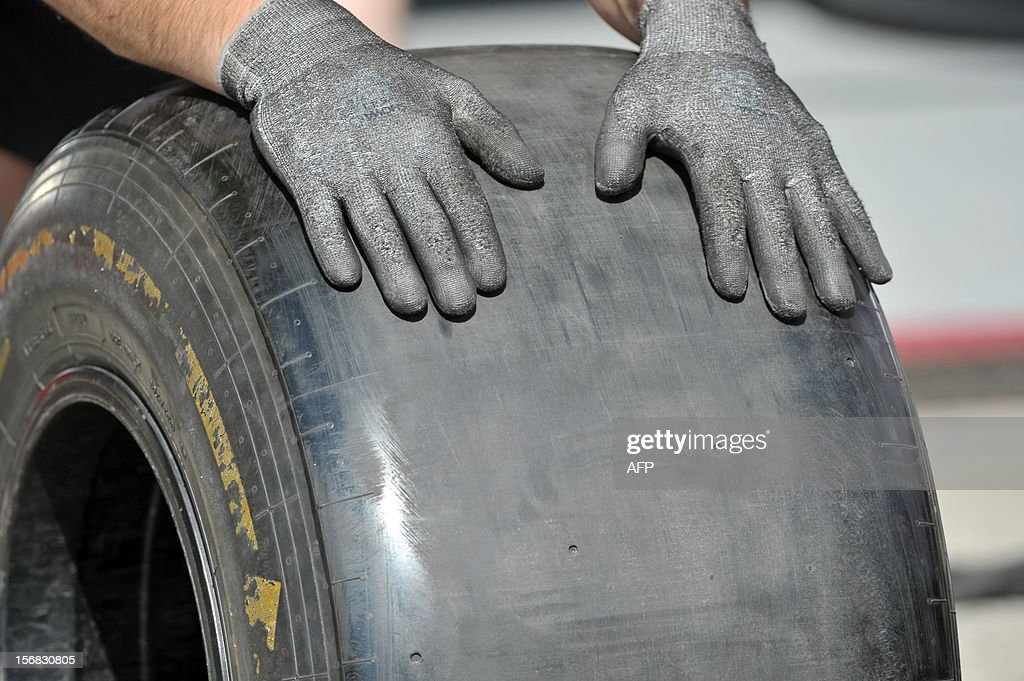A mechanic of McLaren Formula One team holds a tyre at Interlagos motorsport circuit in Sao Paulo on November 22, 2012 ahead of the Brazilian Grand Prix this weekend.
