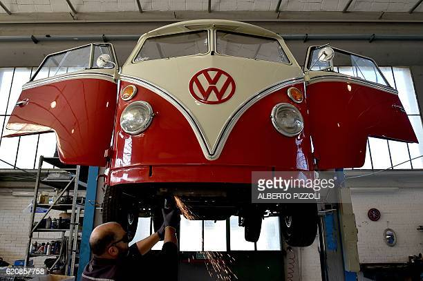 A mechanic of the 'T1 specialist' team works on the restoration of a vintage Volkswagen Kombi bus on November 3 2016 at the garage Nucci in Florence...