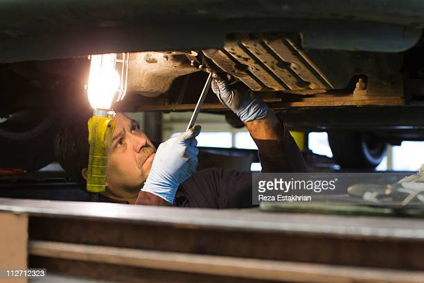 Mechanic opens engine under car