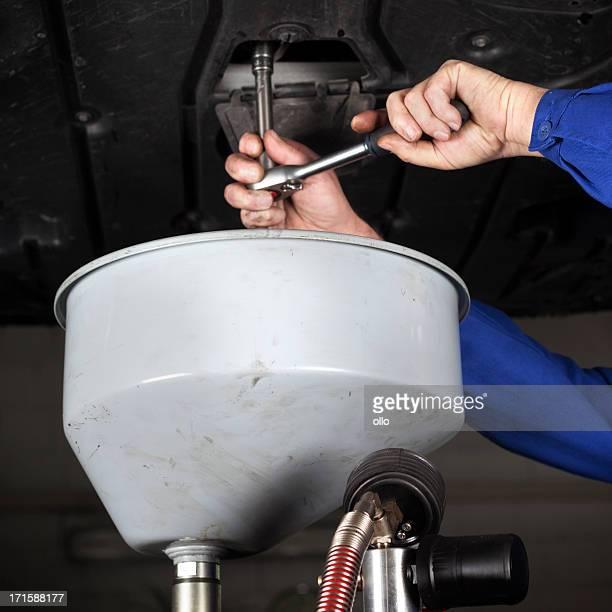 Mechanic opens the oil drain plug of a modern car