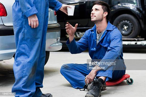 Mechanic passing coffee to colleague on floor
