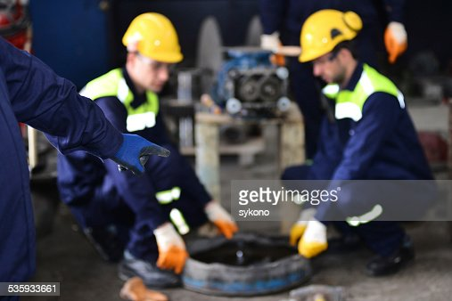 Mechanic pointing at his colleagues : Stock Photo