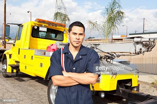 Mechanic posing next to tow truck