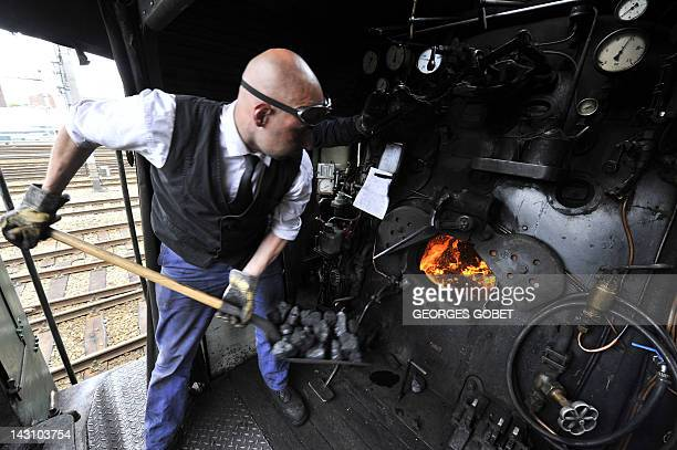 A mechanic puts coal in the boiler of Belgian 1940s locomotive on April 18 2012 at The Gare du Midi in Brussels on the occasion of the presentation...