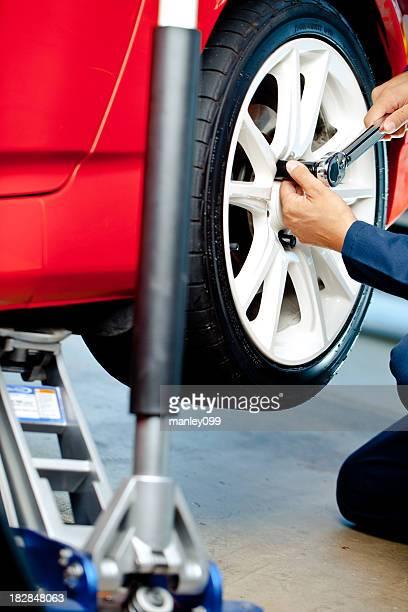 mechanic putting wheel on with jack