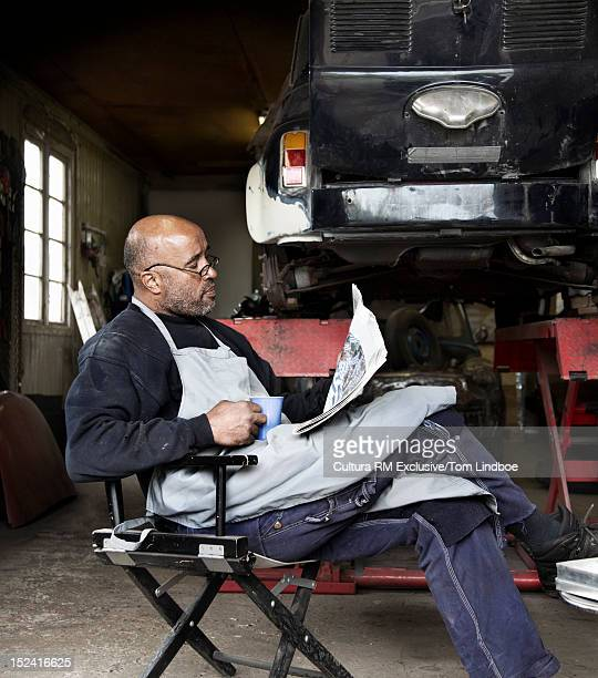 Mechanic reading newspaper in garage