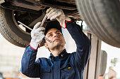 Portrait of a mechanic repairing a lifted car