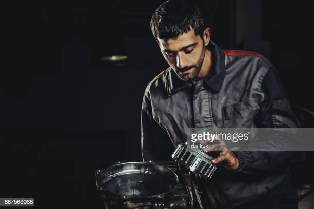 Mechanic repairing automatic transmission