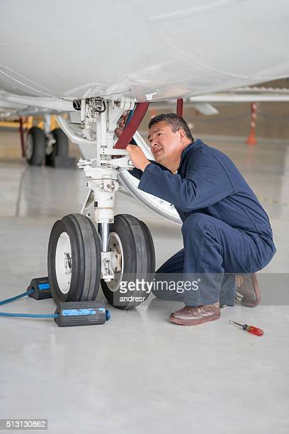 Mechanic repairing landing gear of an airplane