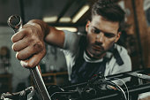 young handsome mechanic repairing motorbike in workshop
