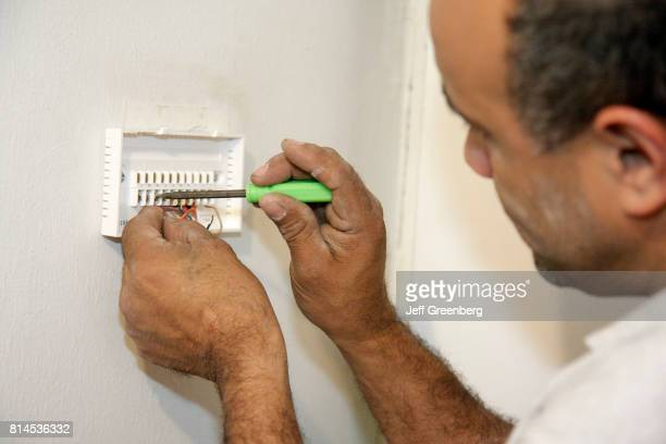 A mechanic repairing the air conditioning at a house at Miami Beach