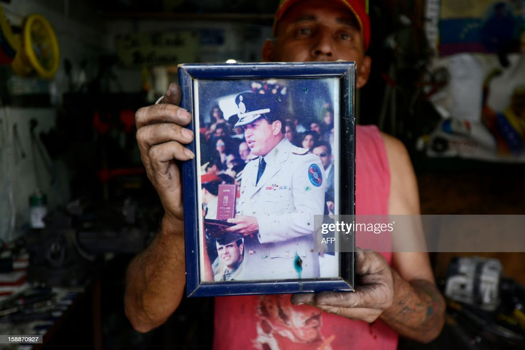 A mechanic shows a picture of Venezuelan President Hugo Chavez at his workshop in Caracas, on January 2, 2013. Chavez is conscious and fully aware of how 'complex' his condition remains three weeks after difficult cancer surgery in Havana, the Venezuelan president's handpicked successor, Vice President Nicolas Maduro, said Tuesday. Chavez underwent his fourth cancer-related surgery three weeks ago in Havana and has been bed-ridden ever since. AFP PHOTO/LEO RAMIREZ