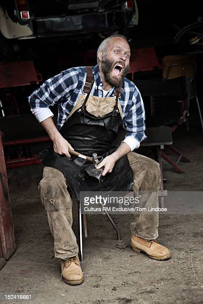 Mechanic smashing his thumb in garage