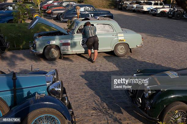 A mechanic speaks with the driver of a 1959 Mercedes 219 Ponton after it crossed the finish line at the Aureum Palace Hotel on the final day of the...