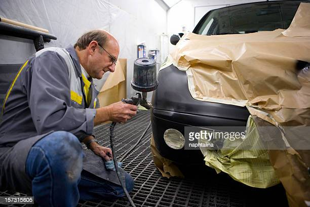 Mechanic spray painting the bumper of a black car