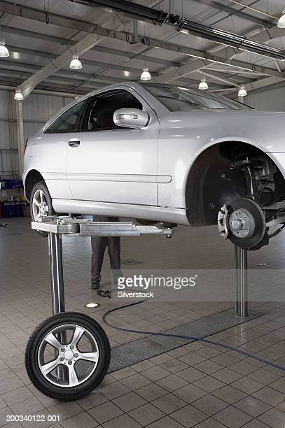 Mechanic standing behind car raised on hydraulic car lift in garage