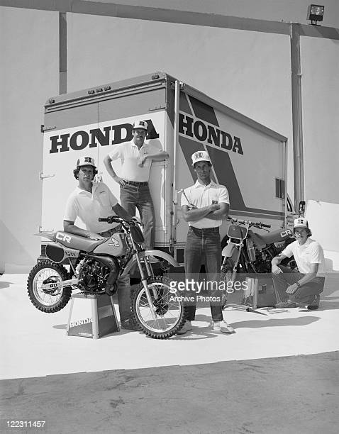 Mechanic standing beside motorbike and truck, portrait