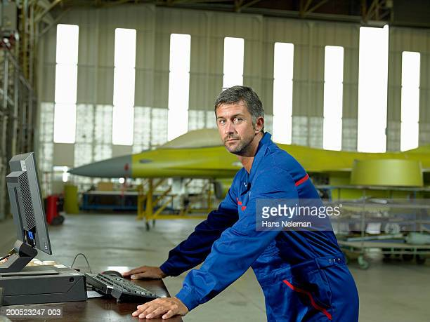 Mechanic standing by computer in aircraft hanger, portrait