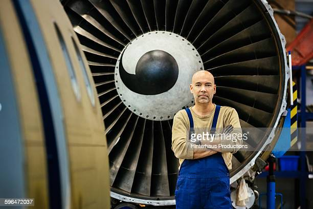Mechanic standing in front of jet engine