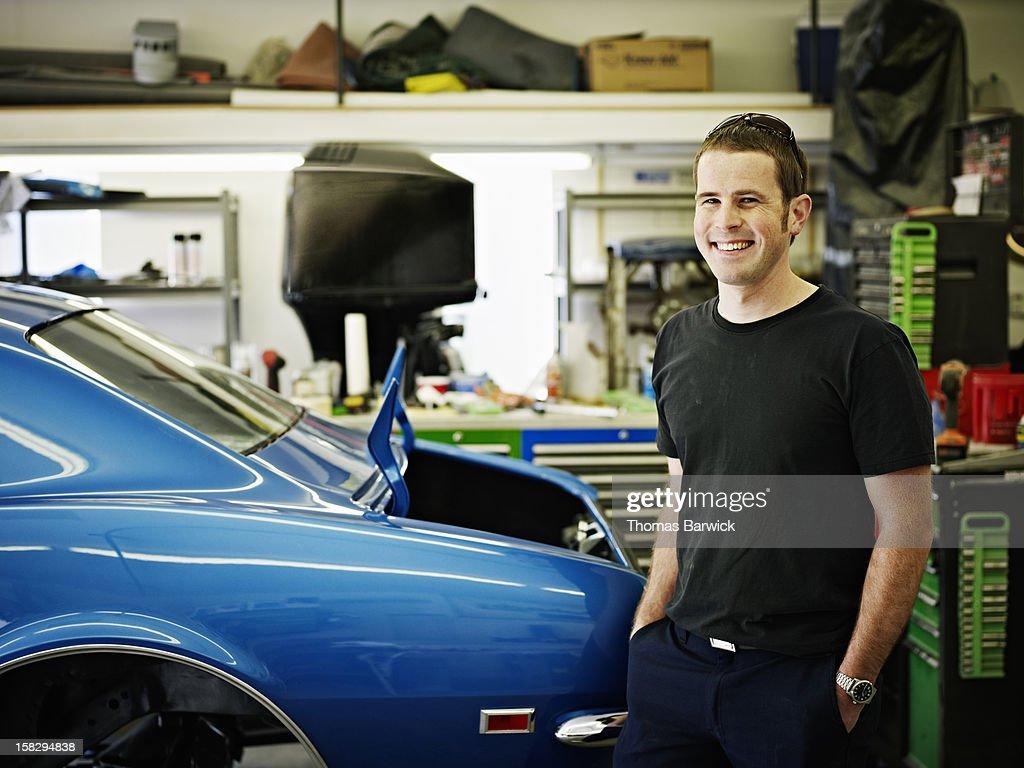 Mechanic standing in garage next to classic car : Stock Photo