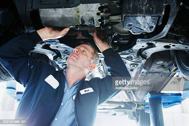 Mechanic standing underneath car to look at engine