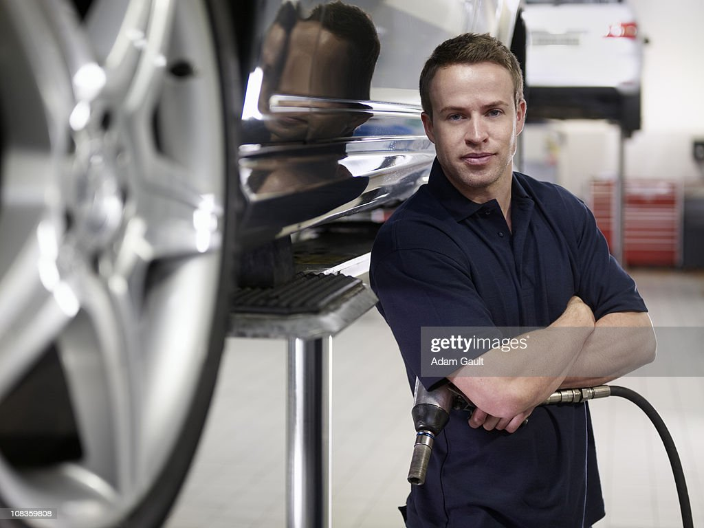 Mechanic standing with car in auto repair shop : Stock Photo