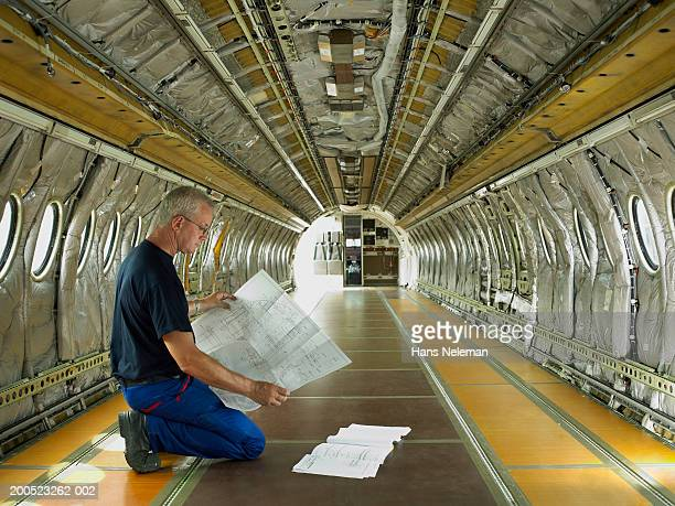 Mechanic studying paperwork in empty aircraft