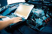 Mechanic using Diagnostic machine tools for car