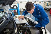 Mechanic using laptop on car at the repair garage