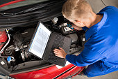 High Angle View Of Mechanic Using Laptop To Repair Car In Garage