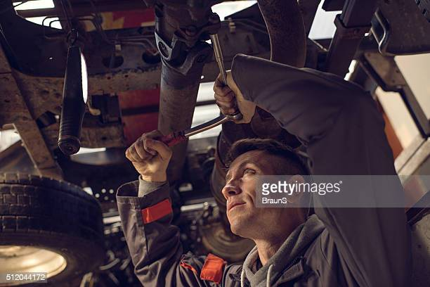 Mechanic using socket wrench while working on a chassis.