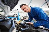 Mechanic using tablet on car at the repair garage