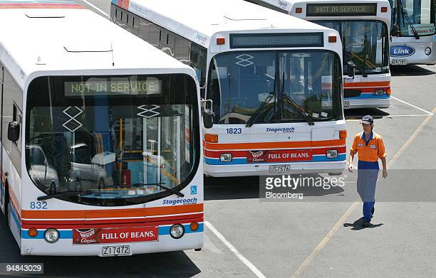 A mechanic walks past Stagecoach buses at a yard in Auckland New Zealand Tuesday November 29 2005 Infratil Ltd bought bus companies in Auckland and...