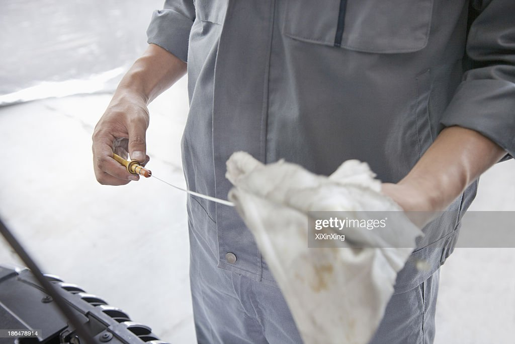 Mechanic Wiping Down Dipstick : Stock Photo
