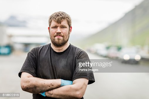 Mechanic with arms crossed standing outside garage