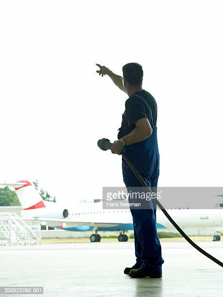 Mechanic with electric cable pointing, outdoors