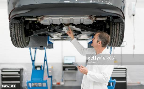 Mechanic working at an auto repair shop checking the chassis of a car