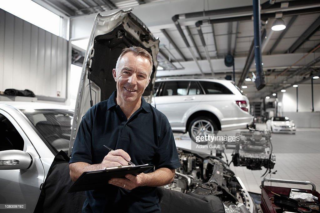 Mechanic working in auto repair shop : Stock Photo
