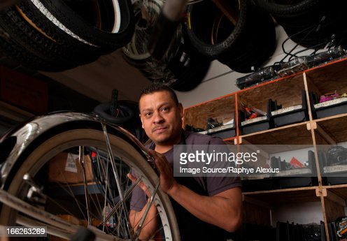 Mechanic working in bicycle shop : Stock Photo