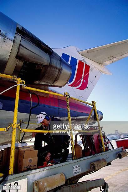 Mechanic working on airplane at Denver International Airport   Location Near Denver Colorado USA