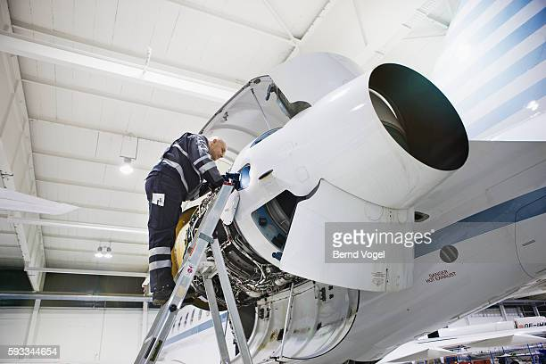 Mechanic working on airplane engine at factory