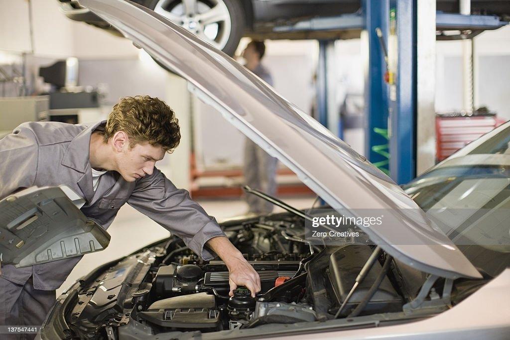Mechanic working on car engine in garage